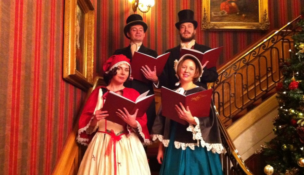 Fezziwig Singers in Victorian costume perform on stairs at Christmas party in Yorkshire